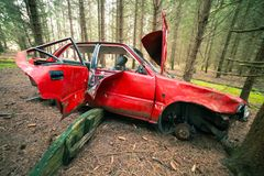 Wrecked Red Car. Red Wrecked car deep in the woods stock image