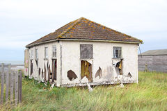 Wrecked ruined bungalow home. Photo of a wrecked weather beaten old chalet bungalow by the sea stock photography