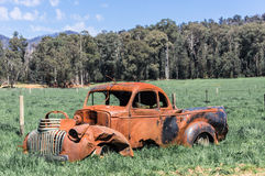 Wrecked, rusted car in an Australian field near Marysville. An old rusted pick up truck in a grassy field near Marysville, Victoria, Australia stock image