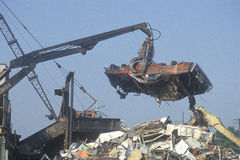 A wrecking crane lowering a demolished automobile Stock Photos