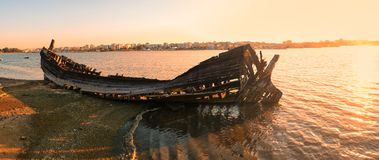 The wrecks of a burned boat on the bank of the Seixal Bay in the. The panoramic view of the wrecks of the old wooden sailboat destroyed and burned on the bank of Stock Photography