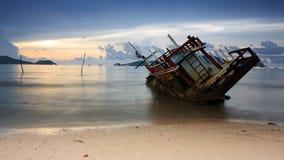 Wreckship auf dem Strand an der Dämmerung Stockbilder