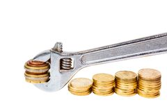 Wrench and coins Stock Images