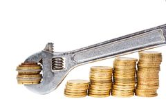 Wrench and coins Royalty Free Stock Photography