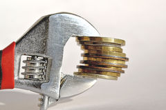 Wrench and coins . The concept of financial reliability Royalty Free Stock Images