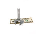 Wrench and dollar bill isolated on white Stock Image