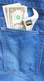 Wrench and dollars in pocket royalty free stock photo