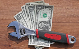 Wrench on dollars royalty free stock images