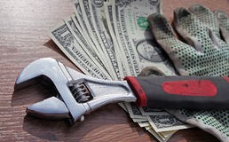 Wrench and gloves on dollars Royalty Free Stock Images