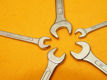 Wrench head detail on orange. Detail of five open wrench heads on contrasting orange background Stock Photo