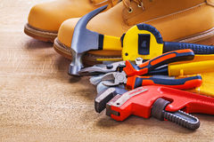 Wrench nippers cutter tapeline hammer work boots Royalty Free Stock Photos