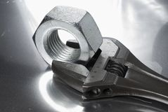 Wrench and nut in monochrome. Wrench and large nut on shiny aluminum Stock Image