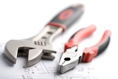 Wrench and pliers over technical drawing isolated