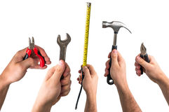 Wrench, pliers, tape measure and hammer in hands of workers Stock Photos