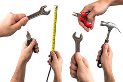 Wrench, pliers, tape measure and hammer in hands of workers Royalty Free Stock Photo