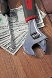 Wrench, screwdriver and dollars stock images