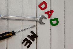 Wrench, screwdriver with text dad and me. On wooden plank Stock Images