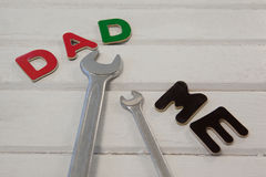 Wrench, screwdriver with text dad and me. On wooden plank Royalty Free Stock Images