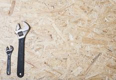 Wrench, small and big one on plywood background. Construction industry concept. Wrench, small and big one on plywood background stock image