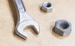 Wrench and some nuts. Wrench with nuts close up royalty free stock images