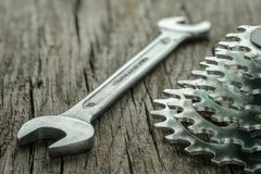 Wrench and sprocket for biycicle. On wooden board royalty free stock image