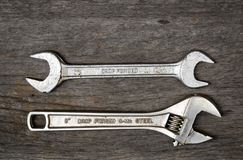 Wrench steel tools. Old wrench steel tools on aging wood background stock images