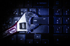 Wrench tool over a laptop on a dark background close up selective focus stock photos