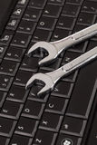 Wrench tool over a laptop Royalty Free Stock Image