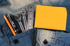 Wrench tools on a denim workers with blank note paper for text, A jeans with engineer tools and note paper. Royalty Free Stock Photography