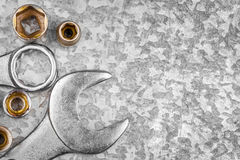 Wrench tools and nuts on a metallic background Stock Photography