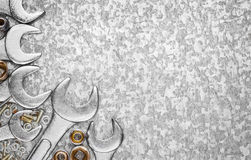 Wrench tools and nuts on a metallic background