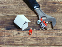 Wrench, toy people and paper Stock Images