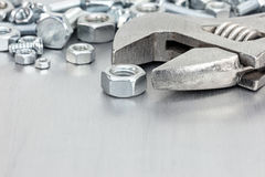 Wrench and various screws for hand work on grey scratched metal Stock Photos