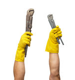 Wrench in yellow rubber gloves Royalty Free Stock Photography
