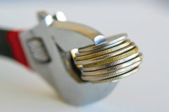 Wrenche and coins . Royalty Free Stock Photos