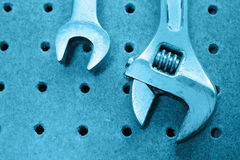 Wrenches. Two wrenches hanging on pegboard, tungsten Stock Photography