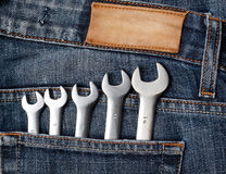 Wrenches in blue jeans pocket. With lable Stock Photos
