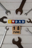 Wrenches date and blocks arranged on wooden plank Stock Images