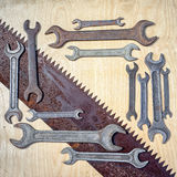 Wrenches. Flat lay frame wiith many old rustic wrenches and laying diagonal saw with copy space for your text. suitable as a background for father`s day congrats Royalty Free Stock Image