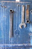 Wrenches hang. From hooks on red pegboard Stock Photo