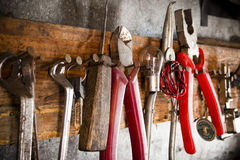 Wrenches, pliers, bulbs, pliers, wire, rope on the nails on the old wooden stand Royalty Free Stock Photography