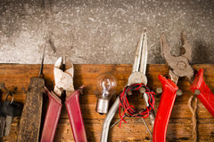 Wrenches, pliers, bulbs, pliers, wire, rope on the nails on the wooden Stock Photos