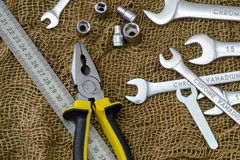 Wrenches, pliers, metal line on a rough brown cloth Stock Photo