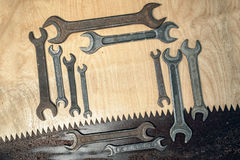 Wrenches. Rectangular frame of old rusty wrenches and saw on a wooden background, diagonal composition, with copy space inside Royalty Free Stock Photo