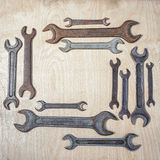 Wrenches. Rectangular frame of old rusty wrenches on a wooden background, with copy space inside Royalty Free Stock Photo