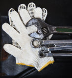 Wrenches spanners plumbing and mechanic glove on dark metal back Stock Images