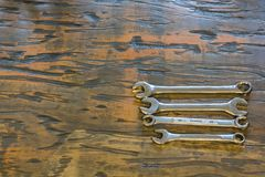 Wrenches on a wood background. Wrenches on a finished wood furface with warm woodgrain Royalty Free Stock Photo
