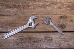 2 wrenchs, большого и немного на деревянной предпосылке Стоковые Изображения RF