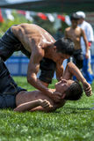 A wrestler helps his defeated opponent from the turf at the Kemer Turkish Oil Wrestling Festival in Turkey. Stock Photos