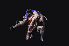 Wrestler performs a throw. Two freestyle wrestlers in red and blue wrestling uniform on black background royalty free stock photos